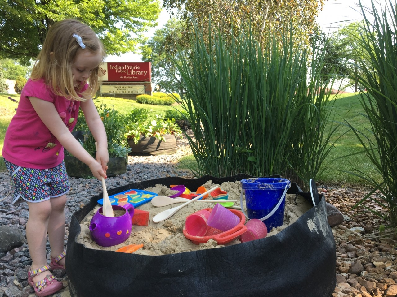 Photo of a young girl playing in the sandbox.