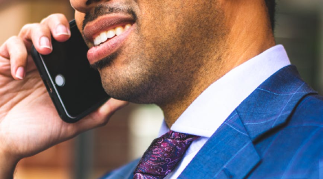 A close-up of a man in a suit speaking on a cell phone.